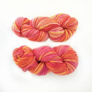 2 skeins of red, orange and pink hand dyed merino yarn