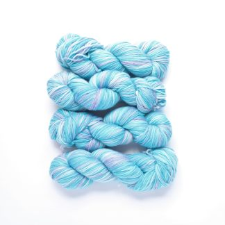 2 skeins of bubblegum hand dyed superwash merino yarn in shades of violet and turquoise