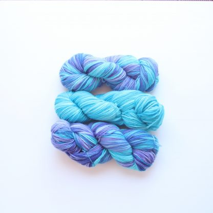 2 skeins of turquoise and violet hand dyed merino yarn with one skein of blue hand dyed merino yarn