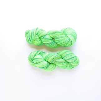 2 skeins of green apple hand dyed lace merino yarn in shades of green