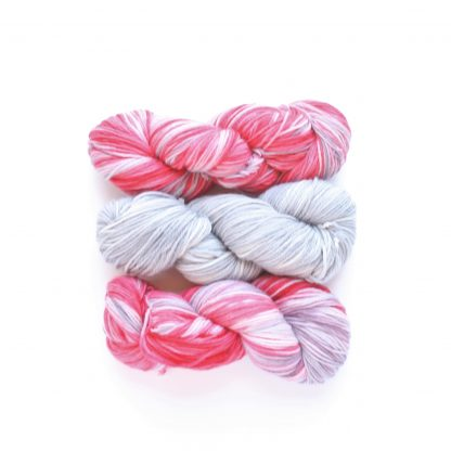 2 skeins of Silver Pink Delight hand dyed merino yarn in silver and pink with 1 skein of hand dyed merino yarn in silver