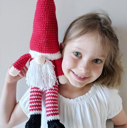 Santa gonk soft toy with tall hat sitting on child's shoulder