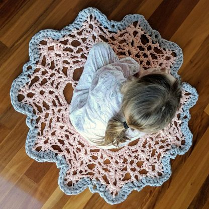 Pink and grey tee shirt yarn round rug with child