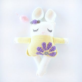 Toy bunny in yellow dress with purple flower applique