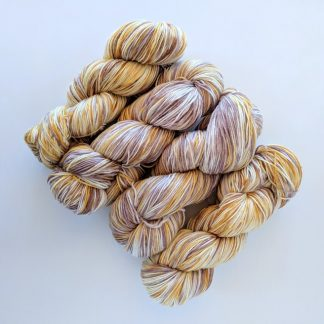 4 skeins of hand dyed fine superwash merino and nylon mix yarn in gold, brown and cream colourway
